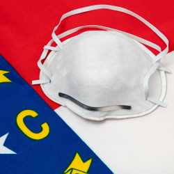 Face mask on top of North Carolina flag