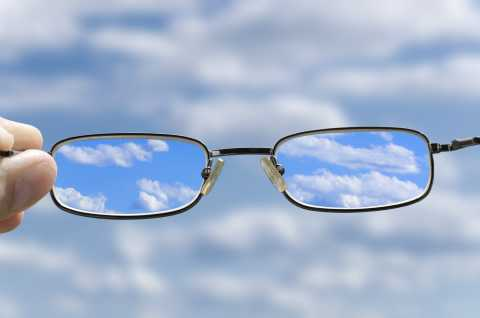 Image of eyeglasses, with clouds in the lenses in focus
