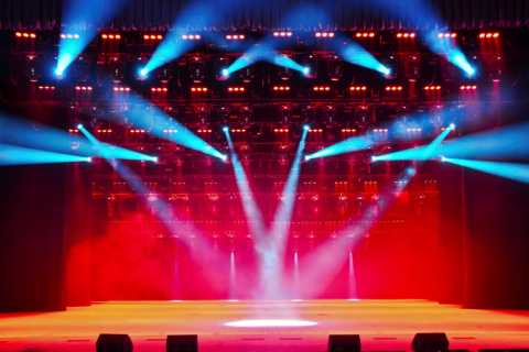 Orange Stage, Pink Curtain, and Blue Lights in a Theater