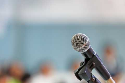 Close-up of microphone with audience in blurred background