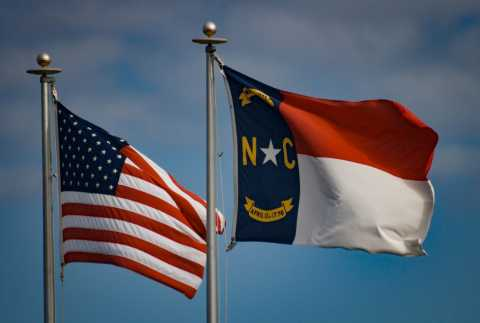 American flag and North Carolina flag blowing in the wind