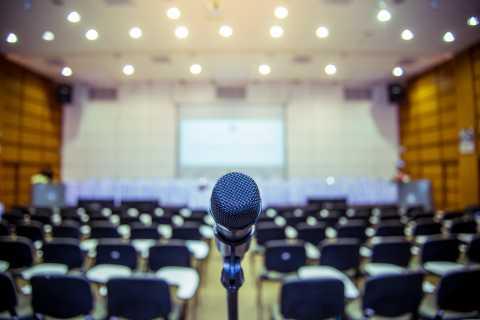 Closeup of microphone, group presentation